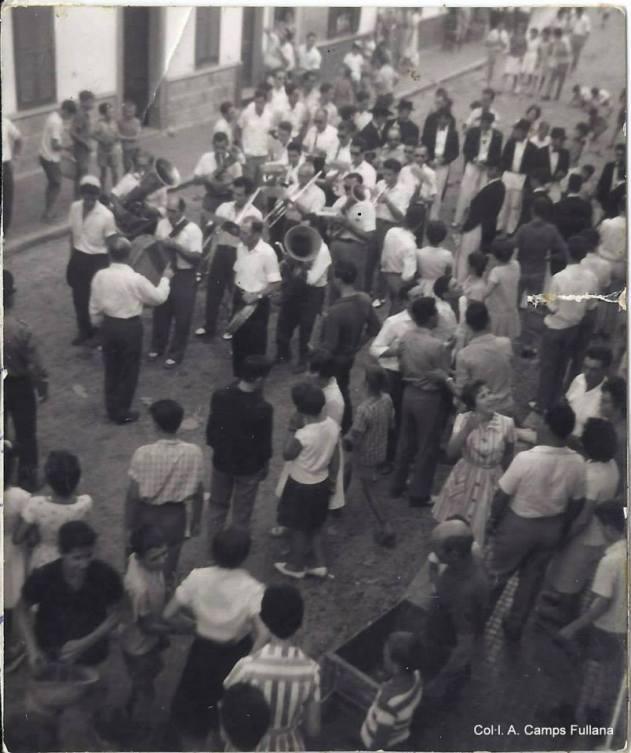 Sant Bartomeu 1962, al carrer Nou, amb la banda de música de Ferreries. Col·lecció d'Antoni Camps Fullana.